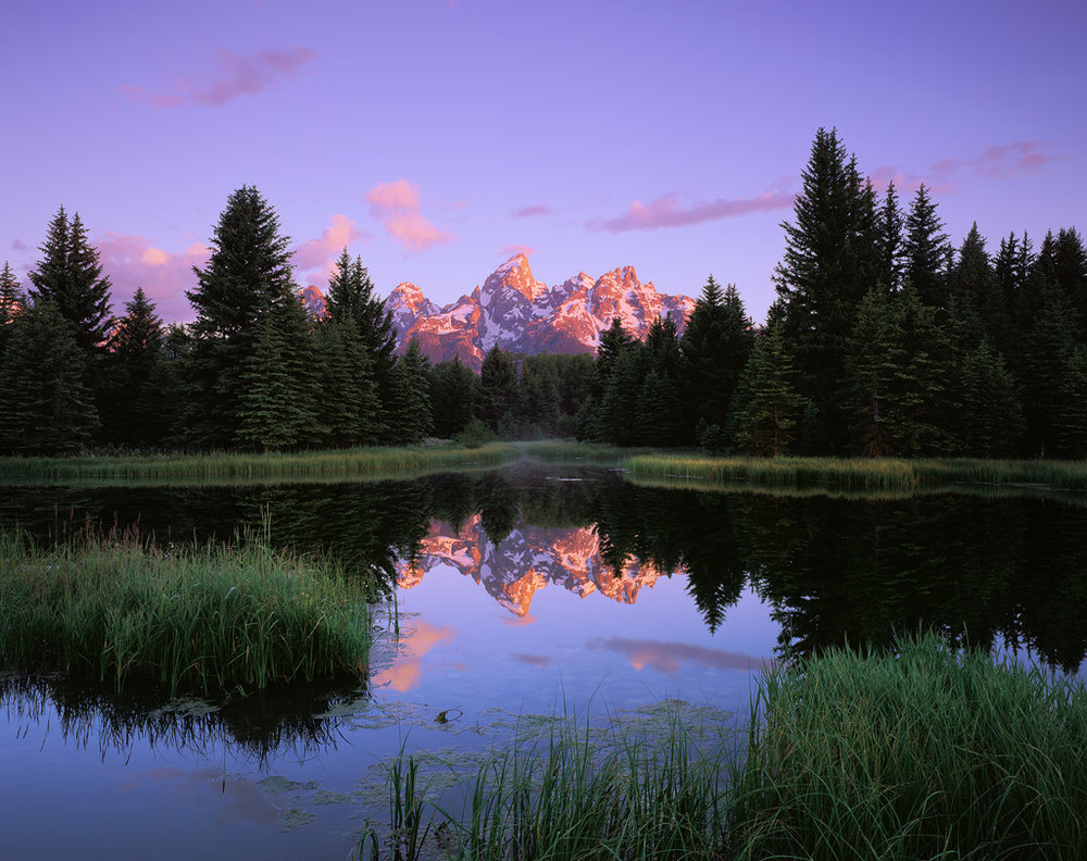 """Teton Reflections"" - Velvia 50 4x5, 90mm lens - 8 seconds at f32, 2 stop soft GND filter. In order to be ready in time I had to set up and focus well before sunrise. I was easily able to focus on the peaks where they met the sky in the dark, as well as the foreground grass where it meets the water. Those objects have strong enough contrast so that focus can be nailed even in dim light."