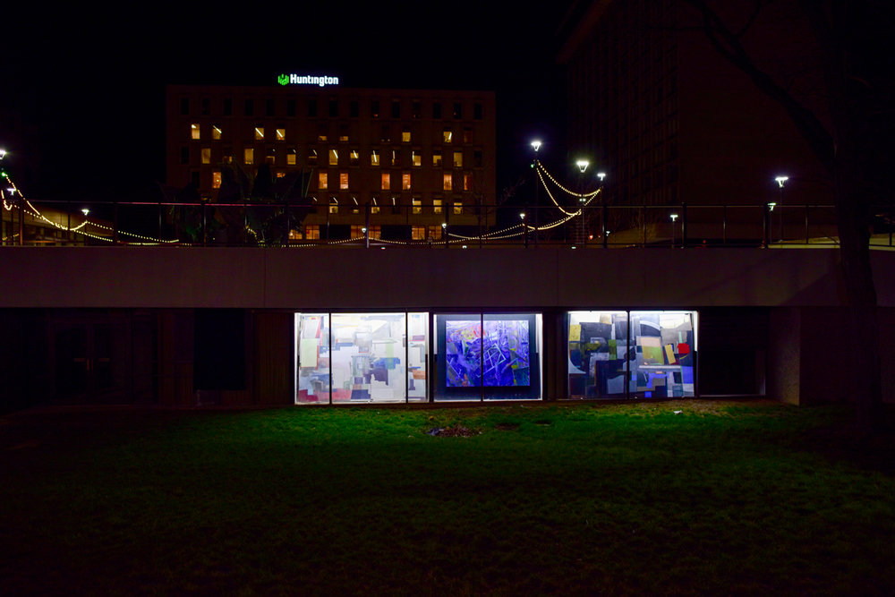Three paintings by Nathan Prebonick are displayed in lower-level windows of this Cascade Plaza building.