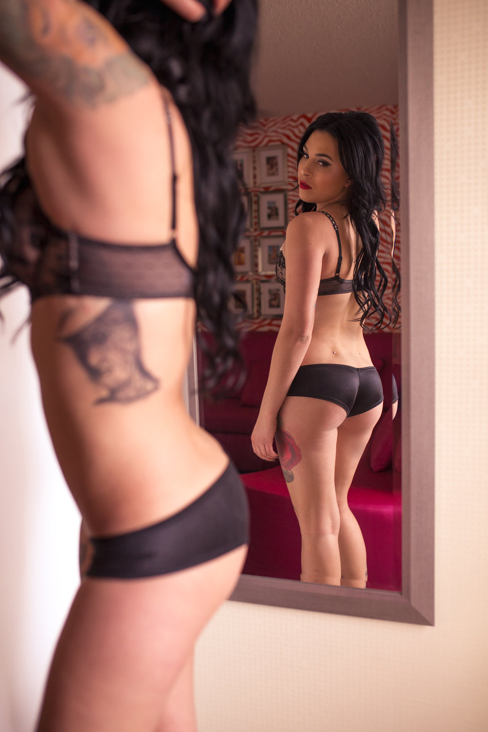 tattooed woman looking in the mirror for a boudoir session in Conifer, Colorado