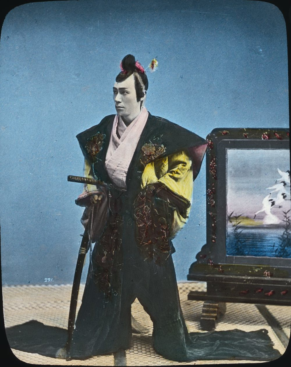 Samurai with long hair drawn upwards into traditional topknot, Japan. Wikimedia commons (link).