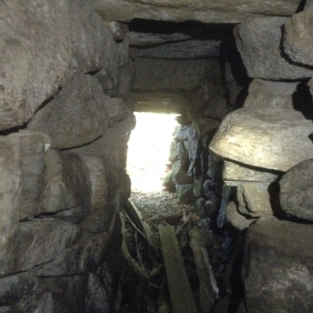 "Above: looking out from the point of transition between the passage and the corbelled chamber (which is behind the viewer). Note the size of the horizontal ""roof slabs,"" all of which are ""underground."" When the visitor approaches the chamber for the first time, the approaching trail leads them to a point at which they are standing on the earth that is above this underground passage and the domed chamber behind."