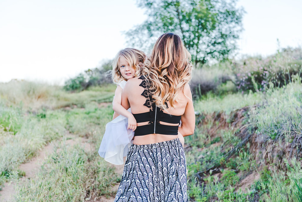 child-looking-over-moms-shoulder@jonesphotographycompany