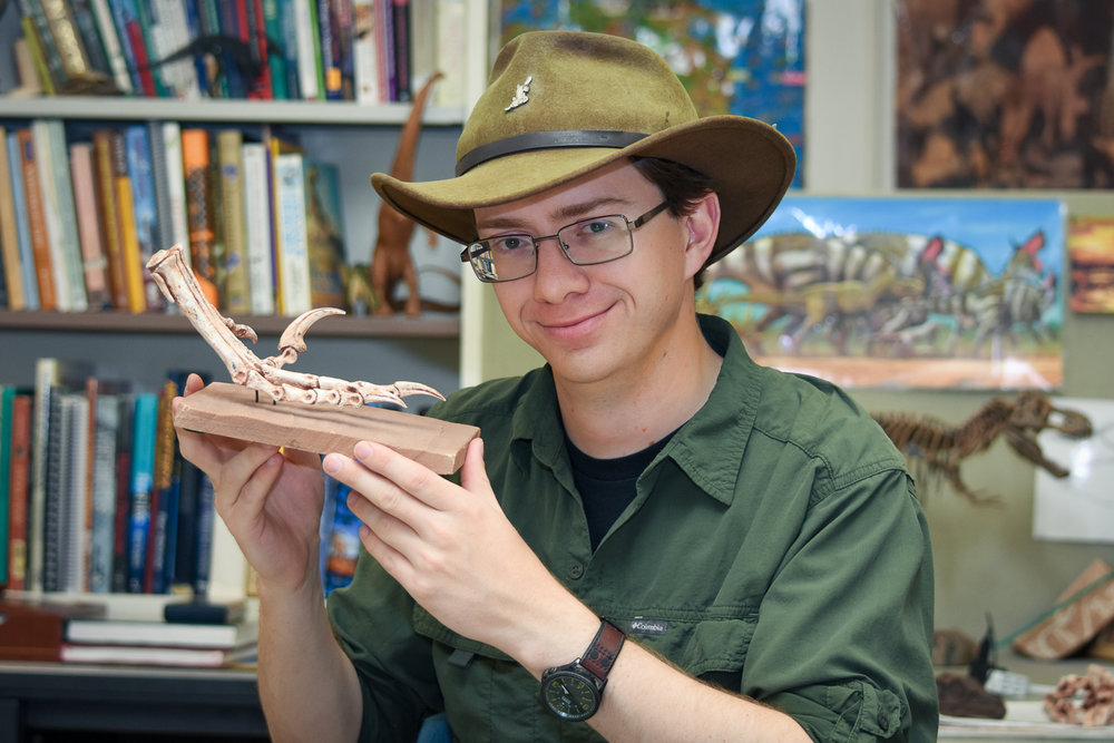 Posing at my desk with the foot of a Velociraptor – same genus as the puppet in the childhood image above.