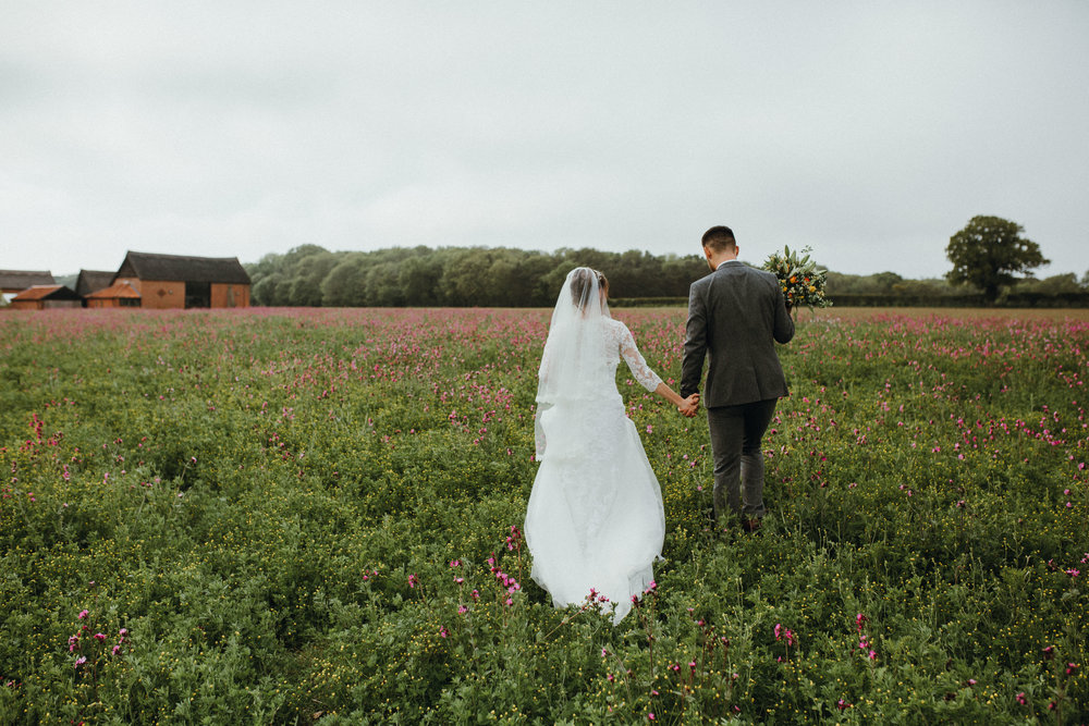 Bride and groom walking through suffolk fields