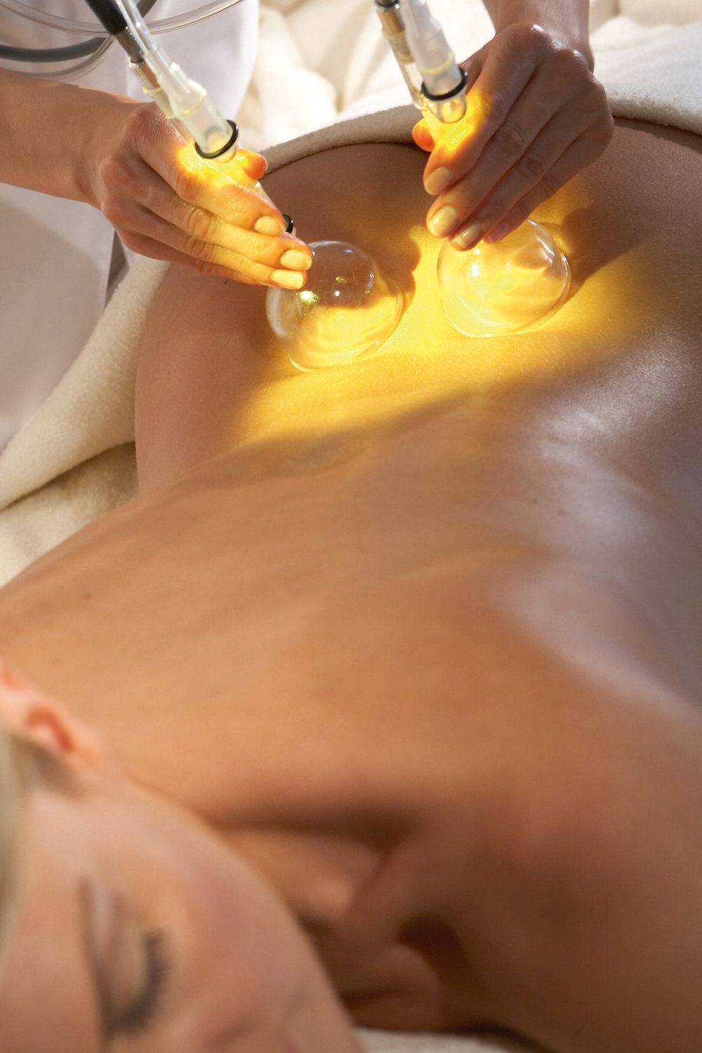 You hear the gentle humming of the pump of the drainage machine as you feel the gliding of its glass cups over face or body. Before starting, the technician applies a vegetal-based oil emulsion mixed with a blend of essential oils on the area being treated. The oil facilitates the gliding of the cups on the skin as it also helps maintain an airtight contact of cup against skin. The pumps alternatively suck in and release the skin layers as the cups are guided by the esthetician or massage therapist following prescribed pathways. The essential oil added to the vegetal oil promotes the movement of fluids below the surface of the skin.