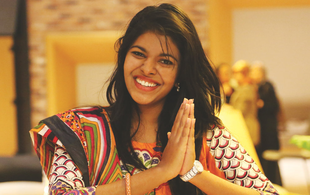 A beautiful Indian woman with 'prayer hands' indicating gratitude