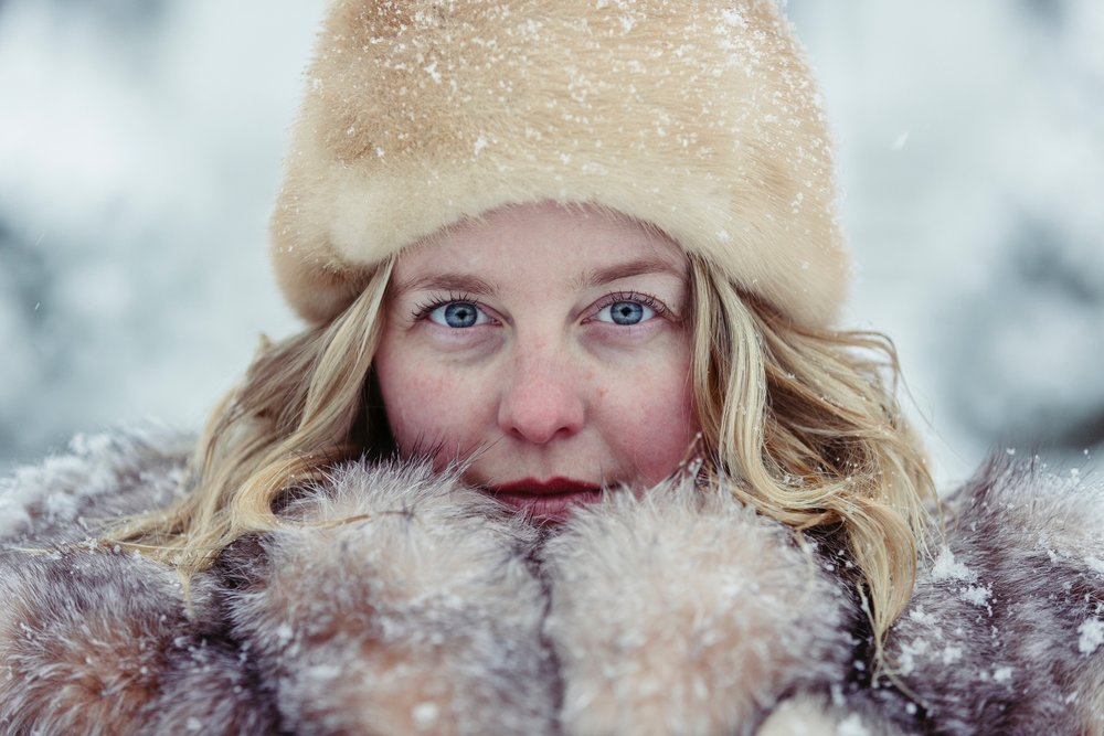 A beautiful blonde woman is bundled up in a fur in the winter snow