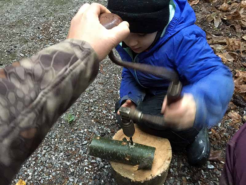 Using the brace to drill holes in the bird feeders