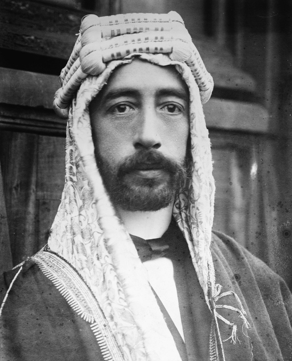 "Undated image of King Faisal, probably from the early 1920s. A tall man of handsome, striking appearance, he was described thus by T. E. Lawrence on the occasion of their first meeting: "" very tall and pillar-like, very slender, in his long white silk robes and his brown head-cloth bound with a brilliant scarlet and gold cord. His eyelids were dropped; and his black beard and colourless face were like a mask against the strange, still watchfulness of his body. "" Originally he seems to have always dressed in Arab costume, even when visiting Europe, but at some point in the mid-1920s he switched to a more western sort of appearance, which is how he looks on the lower-value stamps here. (  Library of Congress  )"