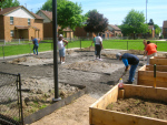 Unthank Plaza & Eliot Square community members spreading over 40 tons of gravel.