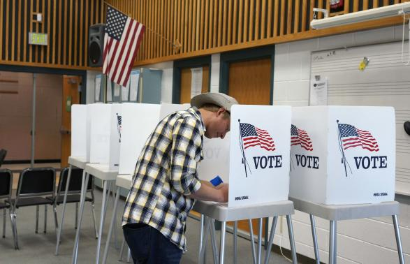 A man fills in his ballot as he votes in the U.S. midterm elections at a polling place in Westminster