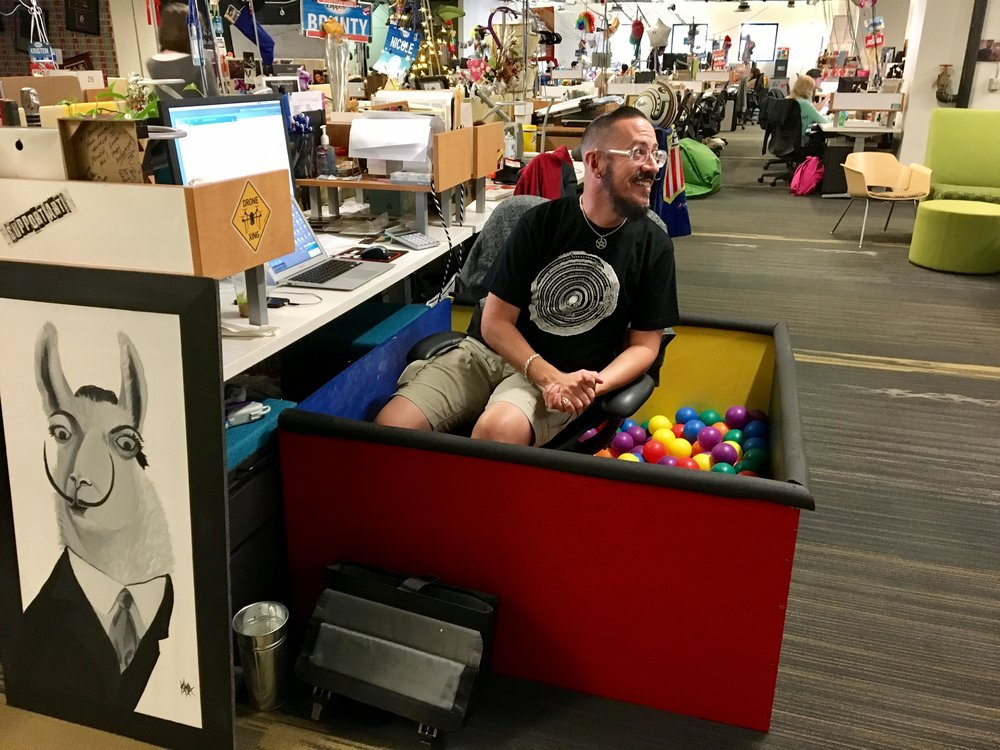 Zappos Insights team member workstation with mini ball pool and portrait of the Dali Llama.