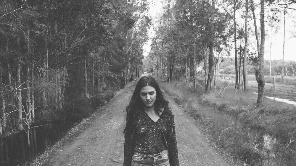 Actress Maddie walking through some of the backroad locations of the video.