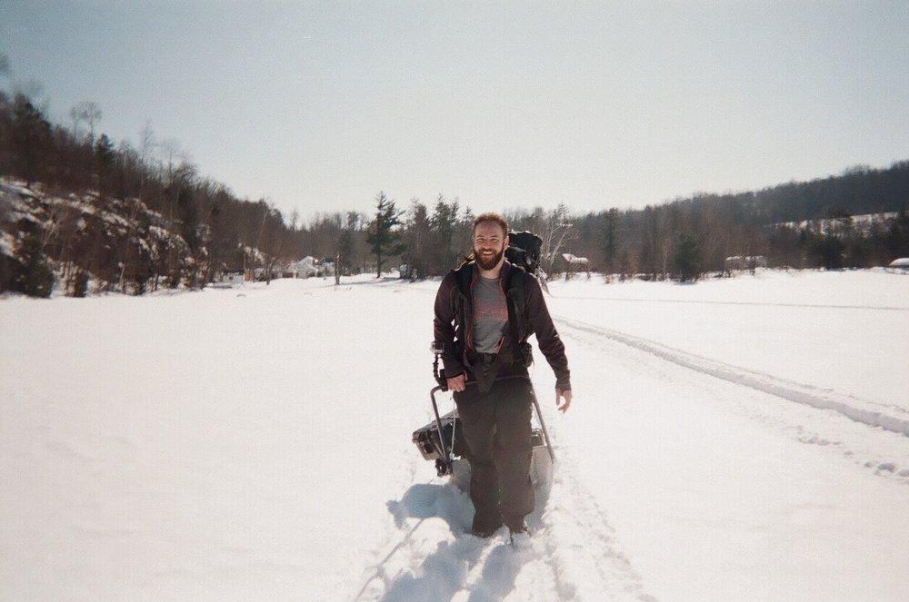 Derek helping move the gear across Kamaniskeg Lake.