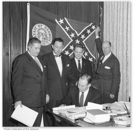 "White supremacist Georgia flag is designed in 1956 by supporters of racial apartheid aka ""Jim Crow."" - John Sammons Bell was the designer."
