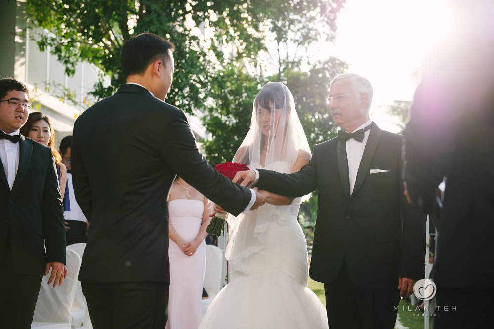 bride's father pass her hand to groom at penang e&o hotel garden wedding