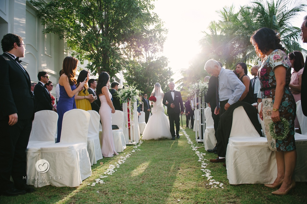 bride and father walk into the garden isle at penang e&o hotel wedding