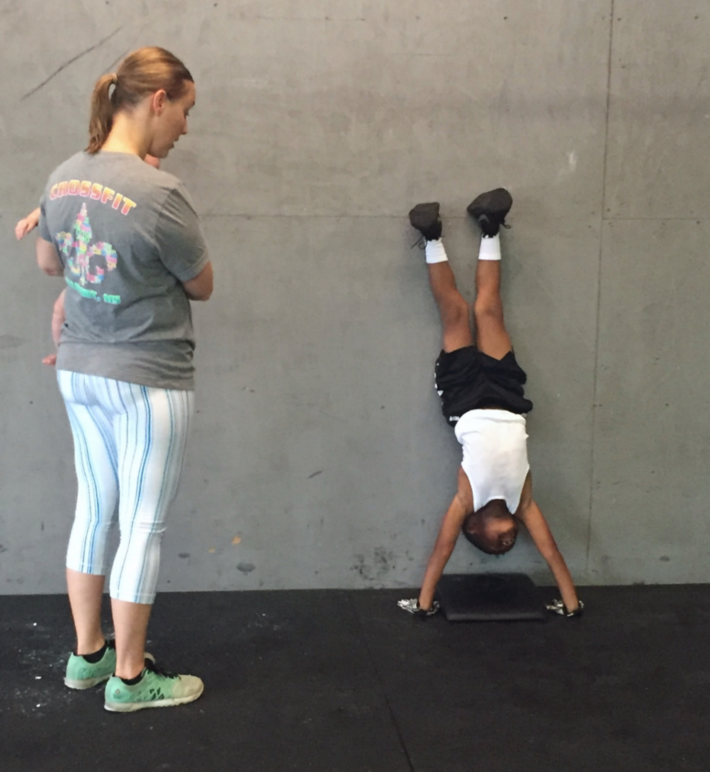 Coach Anna teaching a handstand pushup.