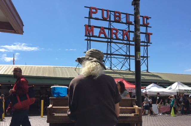 A man set up his piano in the busy Pike Place Market in Seattle.