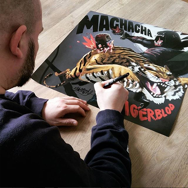 Machacha signing the poster print.
