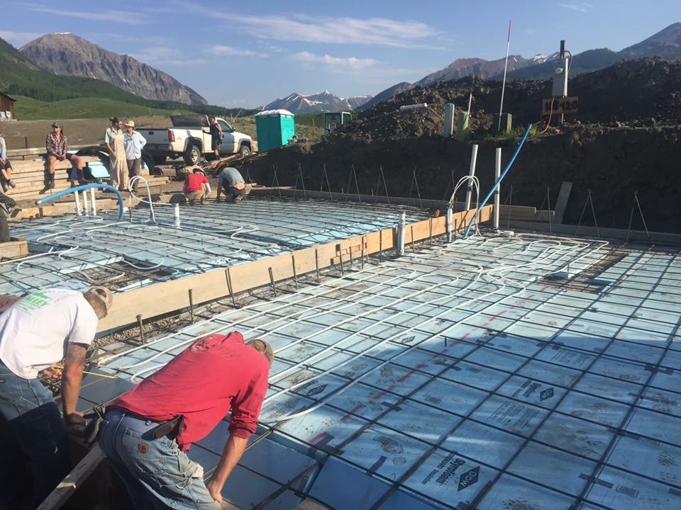 """You can see the """"L"""" shape rebar in the back that form a teepee shape. The blue is the blue board and the white piping is the radiant heating. You can even see the open space where we didn't fill in."""