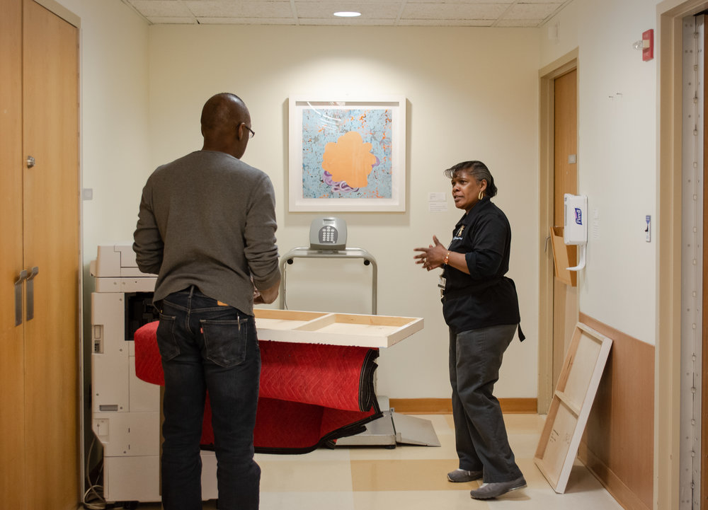 Artist Tim McFarlane with his work speaking with Kim, an employee at the Sidney Kimmel Cancer Center of Jefferon Hospital during installation.