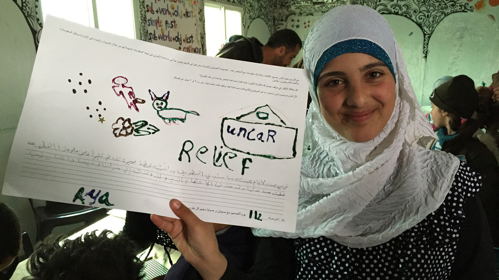 A Syrian teen poses with the drawing she created during a workshop at Za'atari in January 2015.
