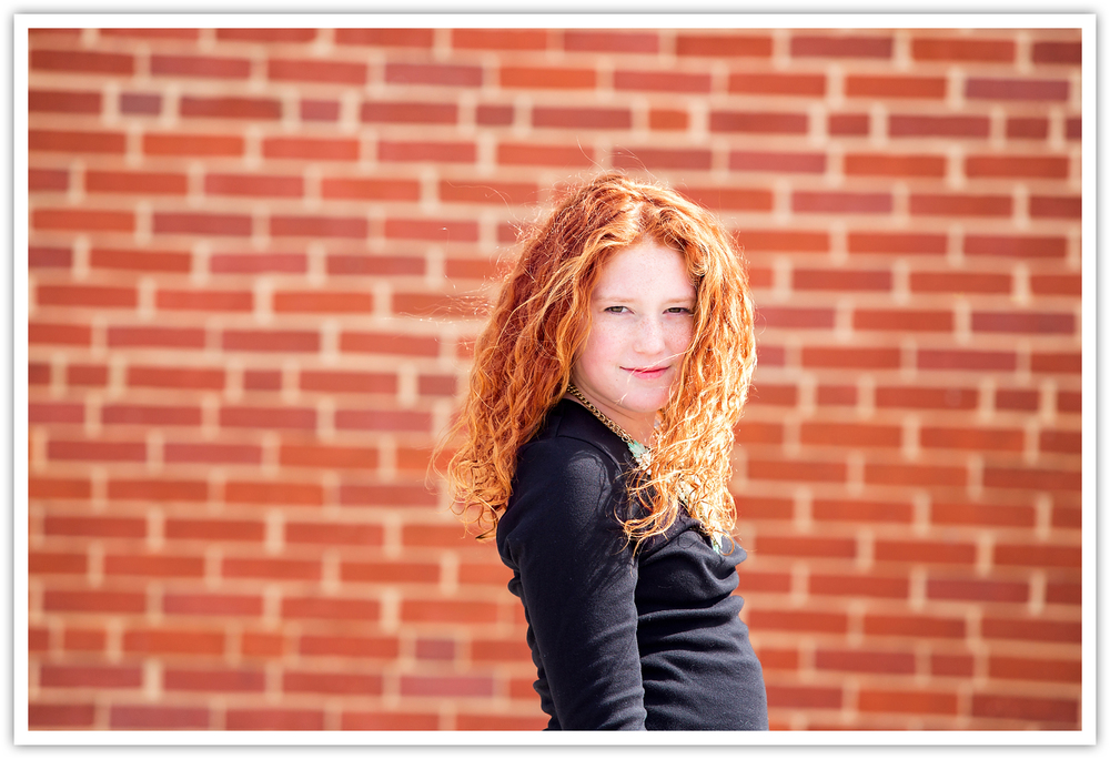 red head on brick wall with hair blowing