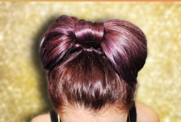 A bow on top! - Pull your hair into a high, looped pony tail on top of your head. Split the bun in half to create 2 loops. Find the middle of the bun, then divide it in half to create 2 loops. Pull the end of ponytail up and over the top of the bow. Pull the ends right between the two loops and secure with a bobby pin underneath. You may want to wrap it if you have a lot of hair left to hide some length. This will create the center part of the bow.