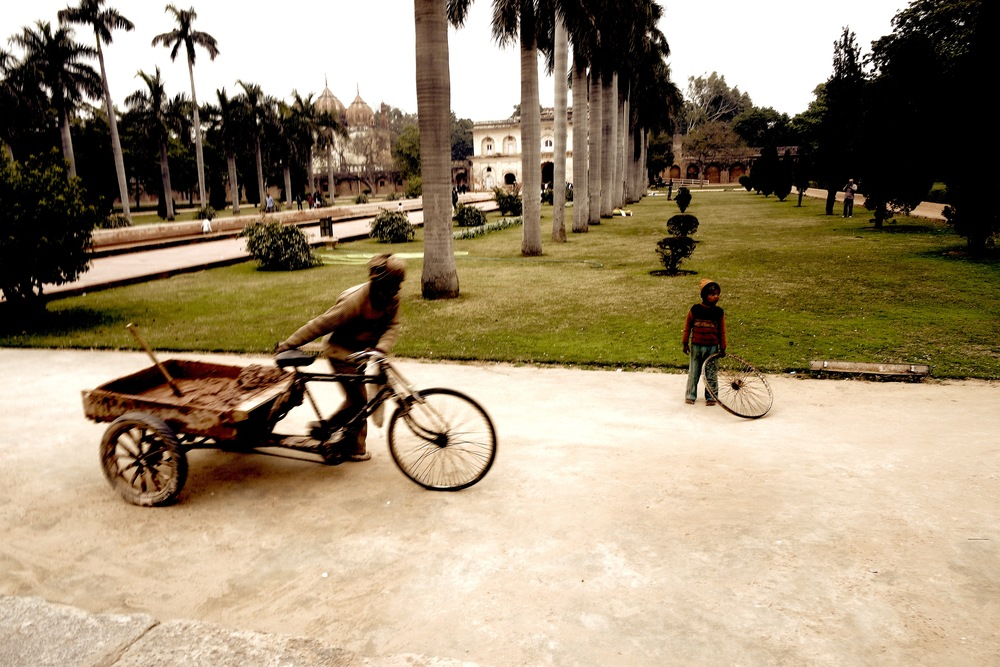 A young boy plays with a wheel while a man uses his wheels to carry materials for restoration at the Tomb of Safdarjung