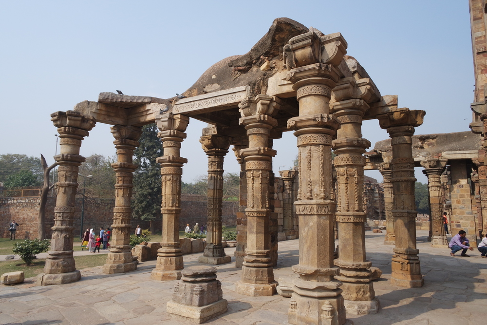 The Quwwat-ul-Islam Mosque in the Qutb Minar complex features columns from pillaged Hindu and Jain temples