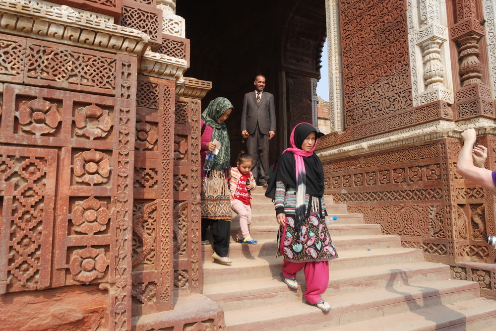 Visitors leave the Alai Darwaza Mosque in the shadow of the Qutb Minar
