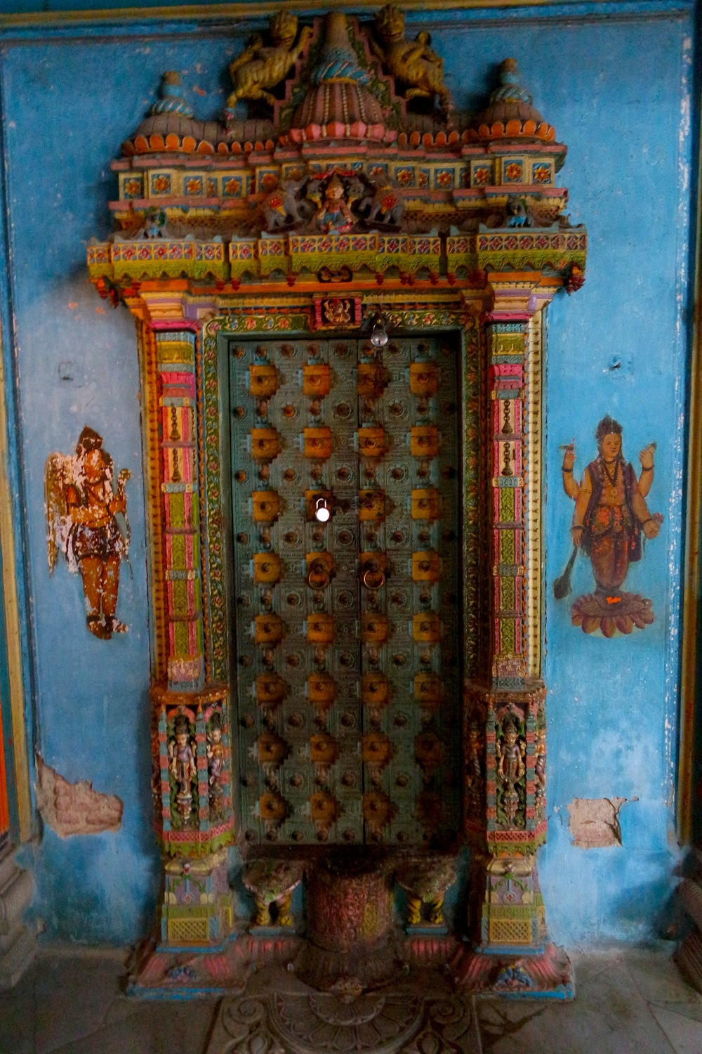An intricately carved and painted door at the wooden Dhundiraj Ganpati Mandir Temple in Vadodara, India