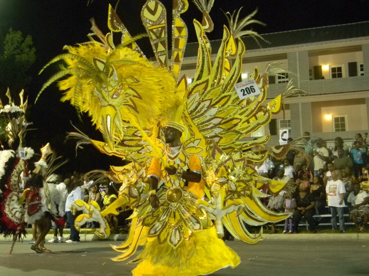 How do the dancers support such enormous costumes during the Junkanoo parade in the Bahamas?
