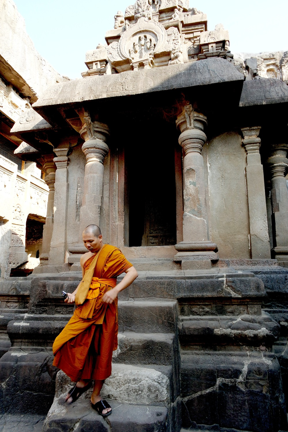 A Buddhist monk in front of the entrance to a shrine at Cave 32