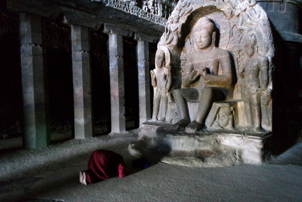 A worshipper lies prostrate in front of the carving of the Buddha in Cave 10