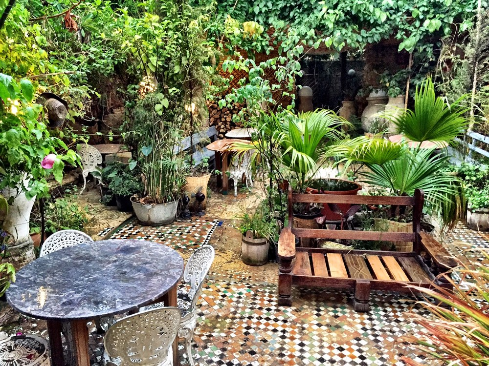 The Ruined Garden features adorably mismatched tables and chairs and is overrun by flowers and other plants