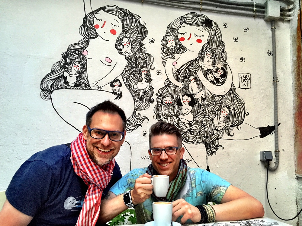 Under the adorable mural by Sara Fratini, Duke and Wally enjoy coffee in the courtyard café of La Casa Invisible in Málaga, Spain