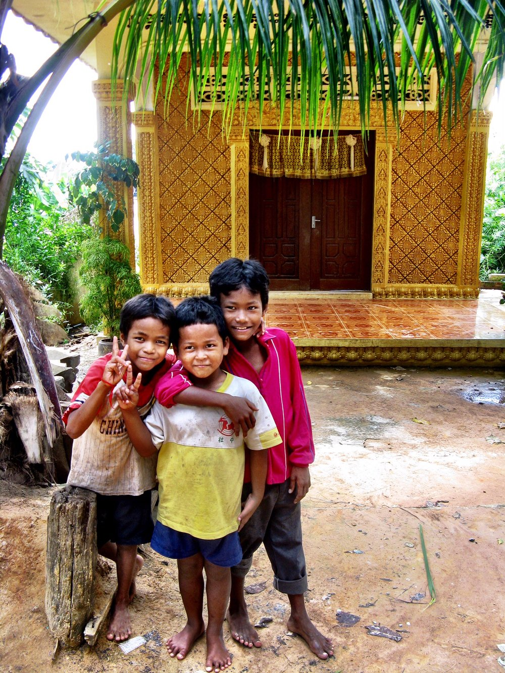 Three boys greet us on the grounds of the Buddhist monastary
