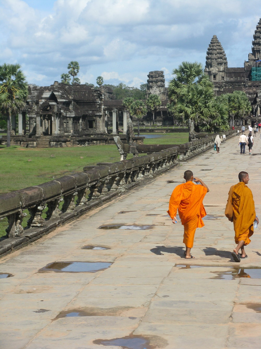 Buddhist monks in saffron robes cross the bridge that leads to the giant temple
