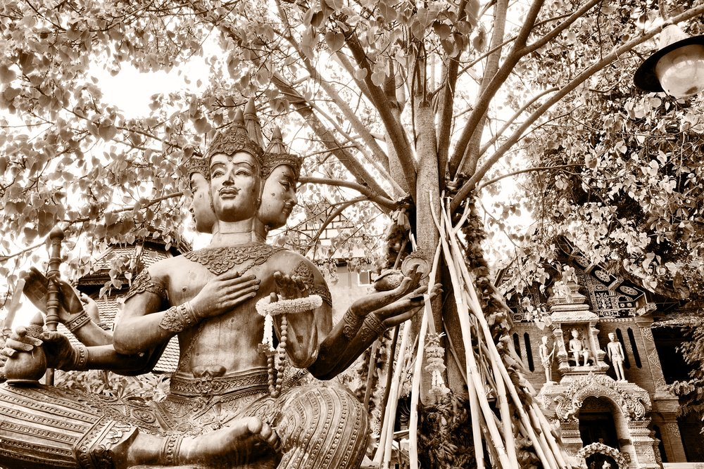 A statue of the four-faced Hindu deity Brahma and a sacred tree