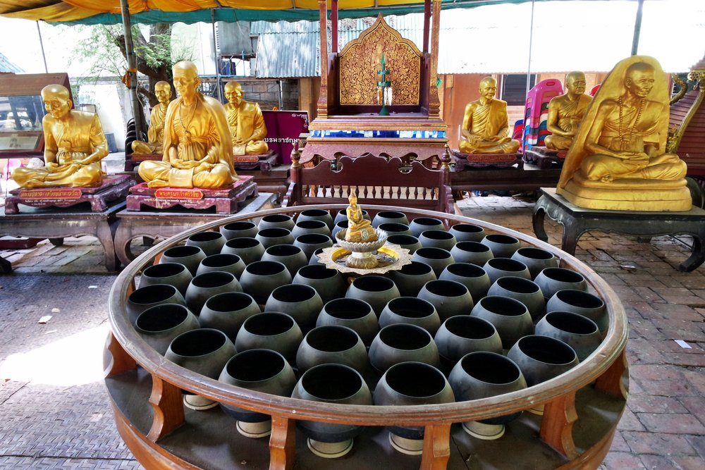 The monks' alms bowls and statues of their famous predecessors in an open-air pavillion