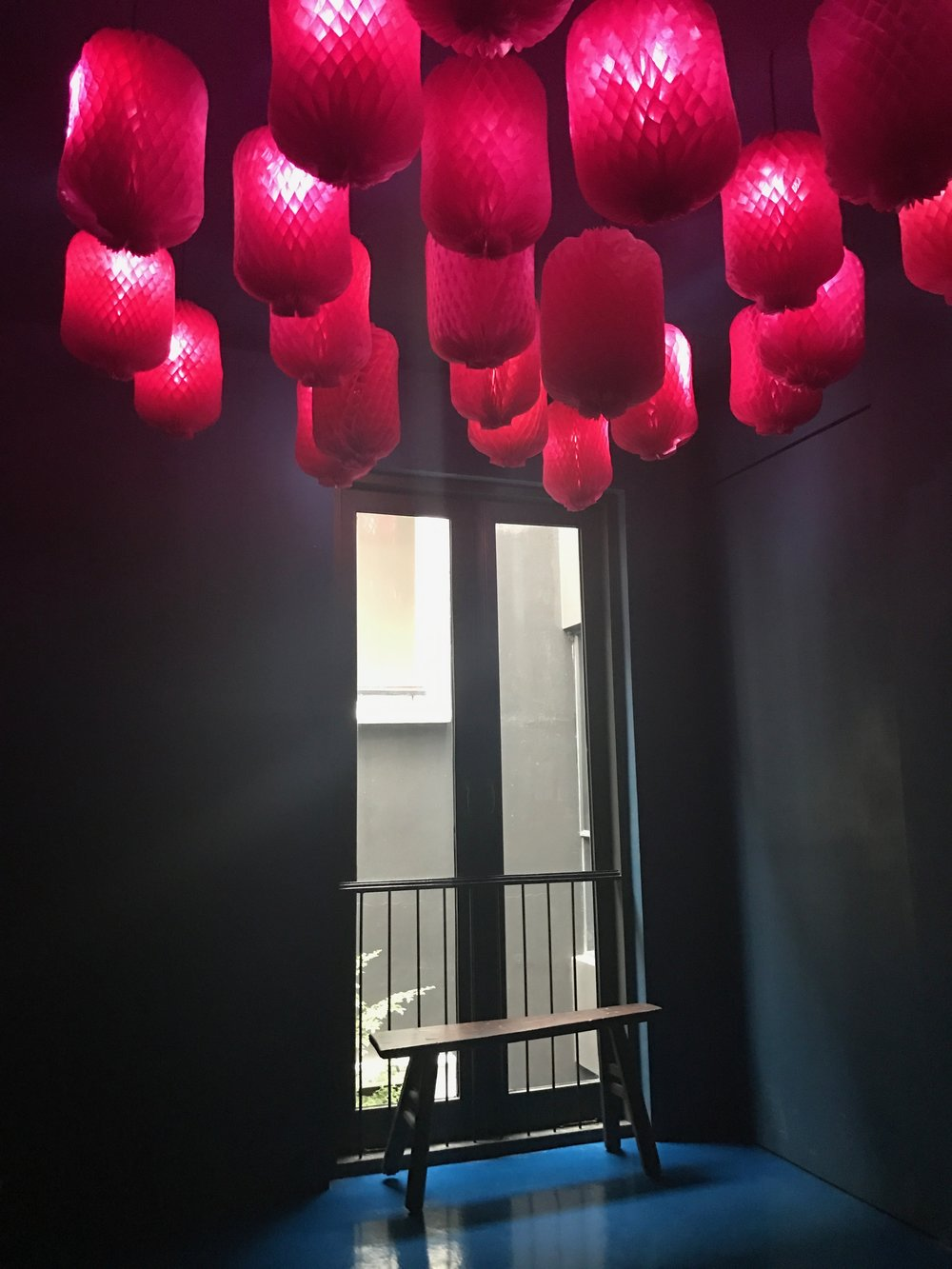Above you, pink paper lanterns offer a bit of modern whimsy