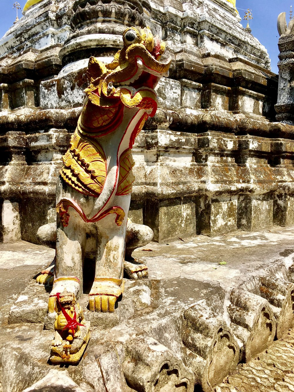 A half-lion, half-dragon creature from Burmese mythology known as a chinthe helps protect the pagoda