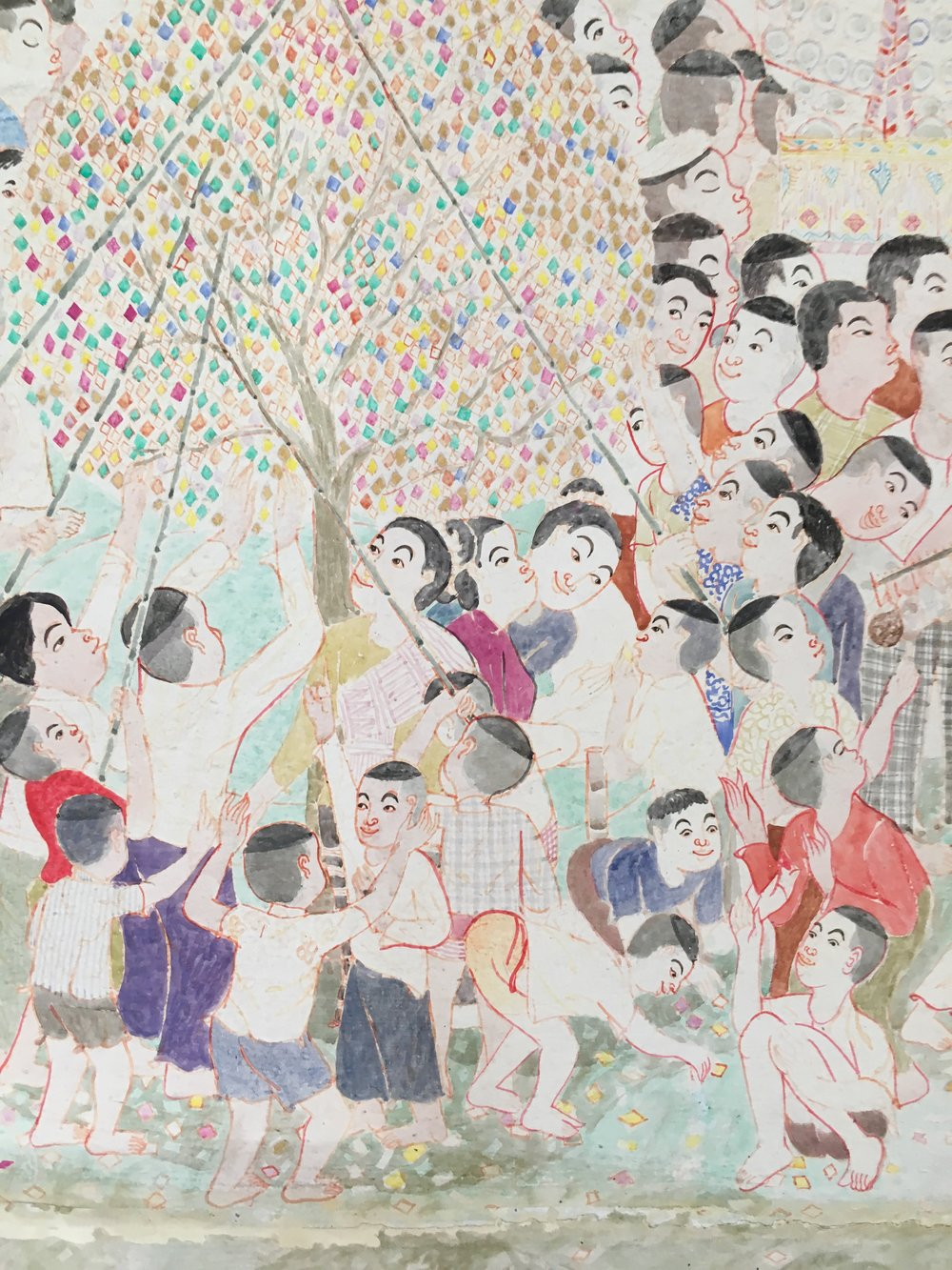 This playful mural by the artist Pornchai Jaima shows people worshipping a sacred tree
