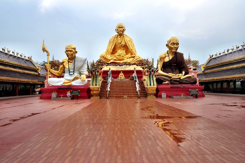Three large golden monks sit atop the back of the complex. The guy in the middle is the Engineer Monk, who's famous around these parts