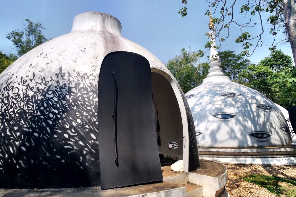 The white domes are modern takes on stupas (the reliquaries of Thai temples) and are covered with cool graffiti