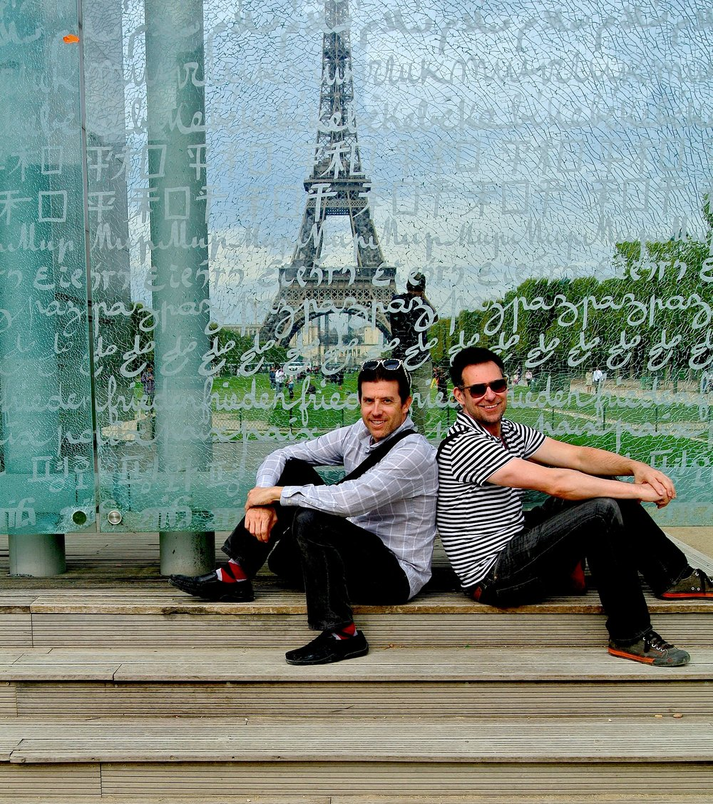 Wally and Duke at la Mur Pour la Paix, the Peace Wall, with the Eiffel Tower visible through it
