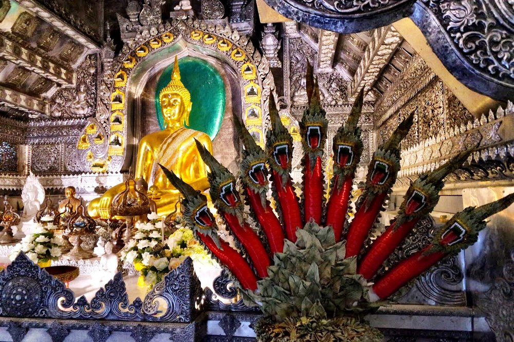 The Buddha image in the ubosot, the main ordination hall with an angry naga fan