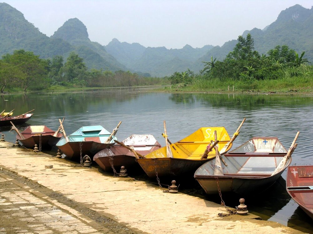 Colorful metal boats line the Yen River, waiting to transport visitors to the Perfume Pagoda